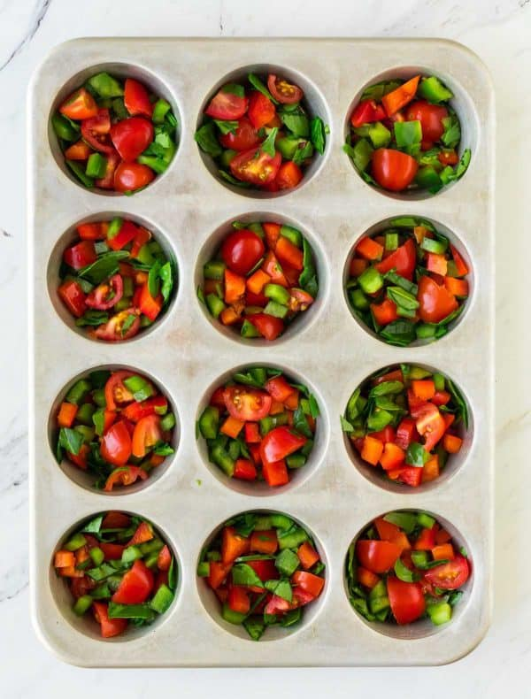 Healthy Breakfast Egg Muffins with spinach, bell peppers, and cherry tomatoes. This delicious recipe is easy to adapt to add more protein, such as breakfast egg muffins with bacon, or swap different veggies!