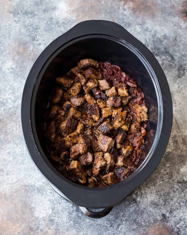 bite sized pieces of seared beef in a slow cooker