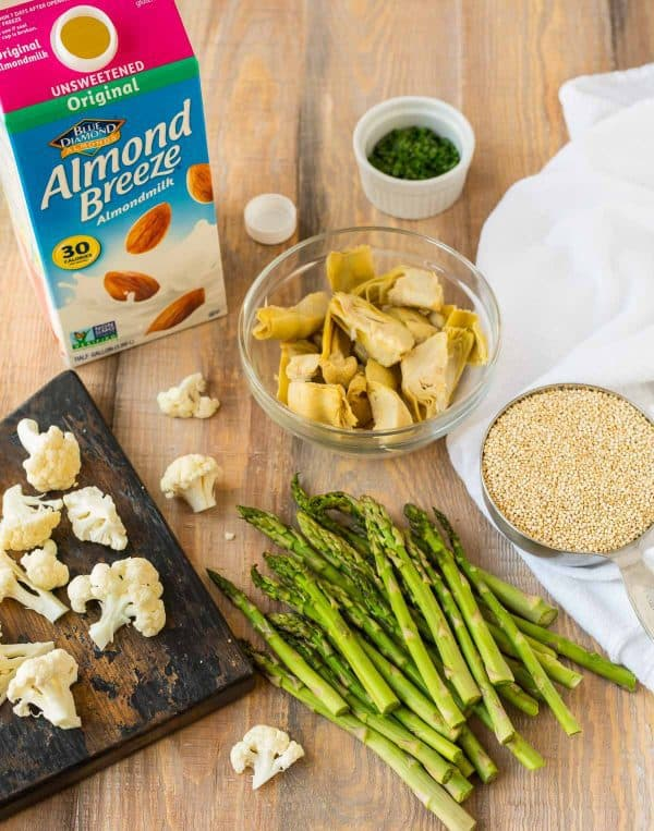 Cauliflower, asparagus, and artichokes are roasted for topping creamy vegan risotto made with quinoa and almond milk.
