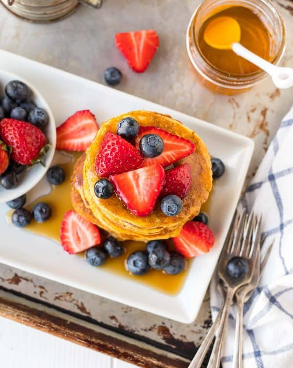 Fluffy Coconut Flour Pancakes topped with fresh fruit and syrup.