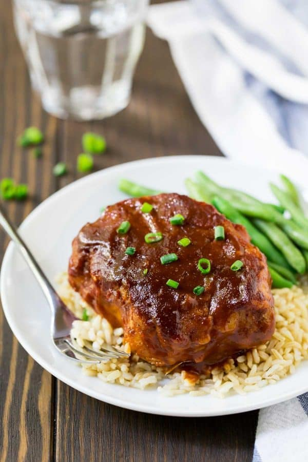 A plate of Crock Pot Pork Chops with rice and green beans