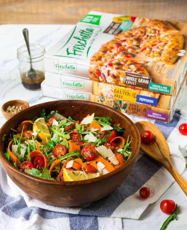 A simple Anytime Arugula Salad with fresh vegetables and Parmesan shavings served with pizza.