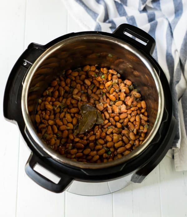 An Instant Pot with cooked pinto beans inside