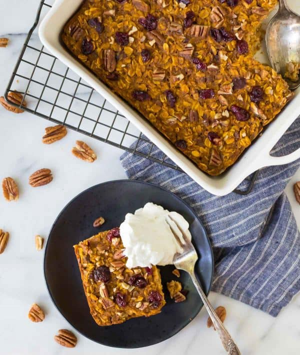 Healthy Pumpkin Baked Oatmeal with dried cranberries, maple syrup, and pecans. No sugar! Super filling and absolutely delicious! Perfect for fall mornings and on-the-go healthy snacks.