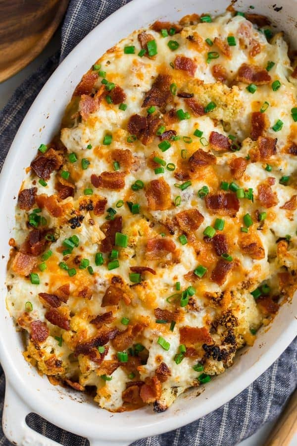 Creamy cauliflower casserole in a baking dish with bacon and cheese