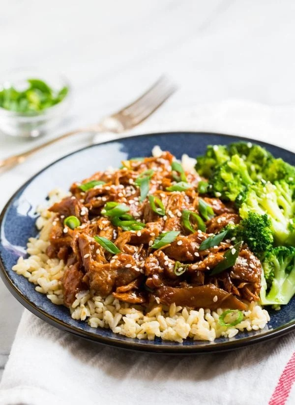 Shredded chicken in a sauce served on a plate with rice and broccoli