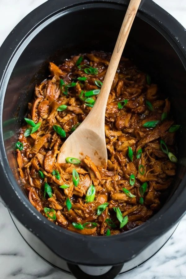 Easy slow cooker chicken in a crockpot with a wooden spoon