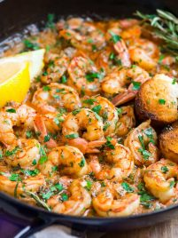 A Skillet of Healthy Garlic Butter Shrimp with Lemon Slices and Rosemary