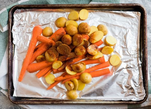 A sheet pan lined with foil with potatoes and carrots