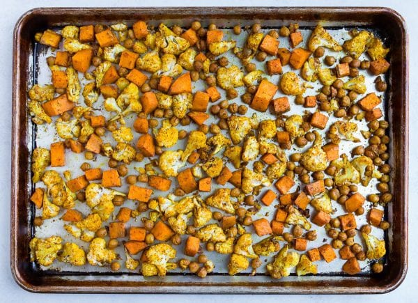 A sheet pan of roasted cauliflower, sweet potato, and chickpeas