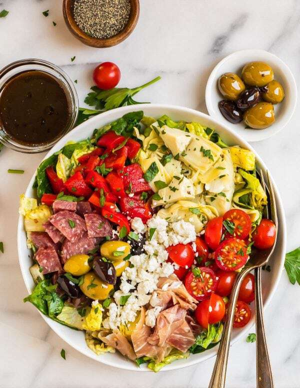 A white bowl of Italian Antipasto Salad with romaine, salami, vegetables, olives, and prosciutto with balsamic dressing