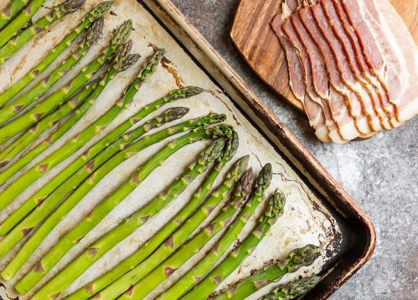 Bacon Wrapped Asparagus being assembled on a baking sheet