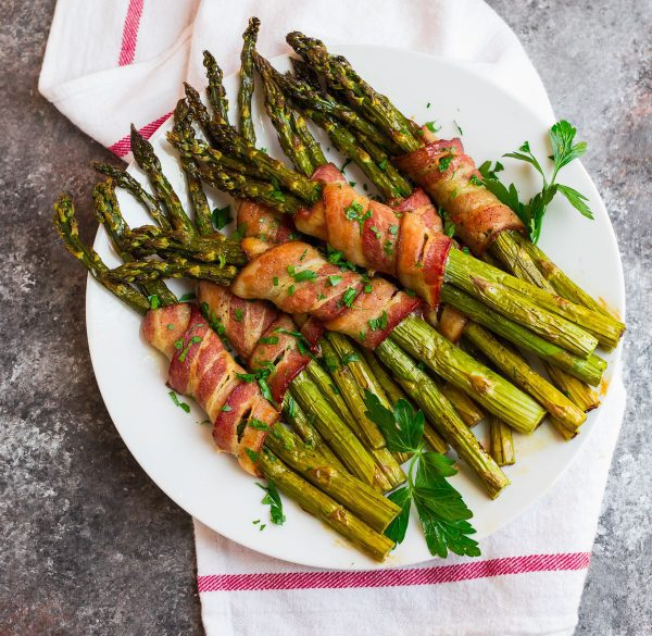 An overhead shot of delicious Bacon Wrapped Asparagus on a white plate