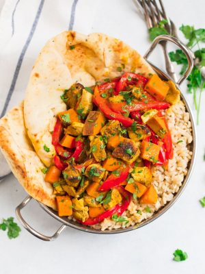 Slow Cooker Chicken Curry thighs with an Indian coconut milk sauce and vegetables, served over rice