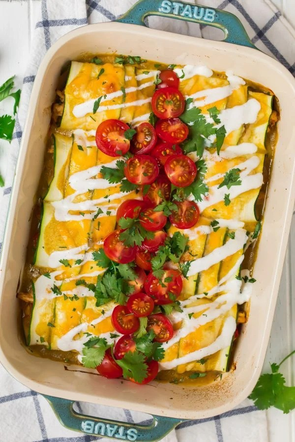 Baked zucchini enchiladas with chicken, topped with green sauce, white sauce, and cheese, in a casserole dish