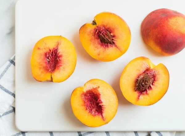 Juicy, fresh peach halves on a cutting board for Baked Peaches.
