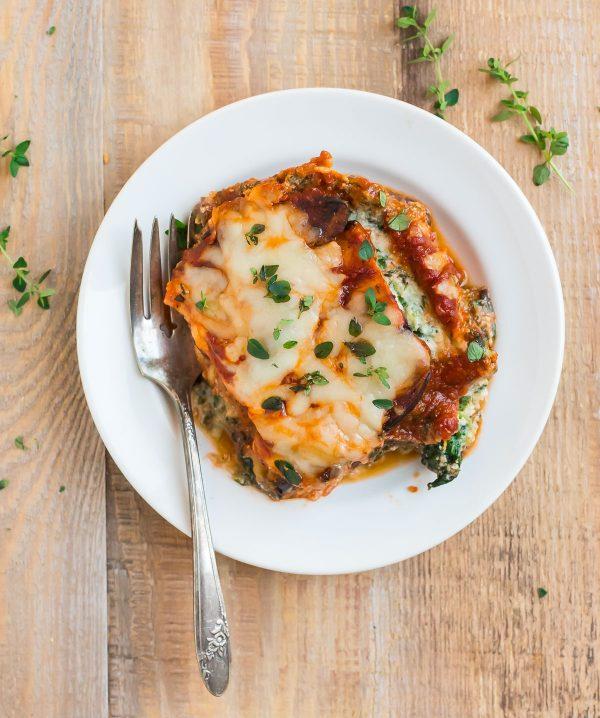 A cheesy, delicious slice of Eggplant Lasagna on a white plate.