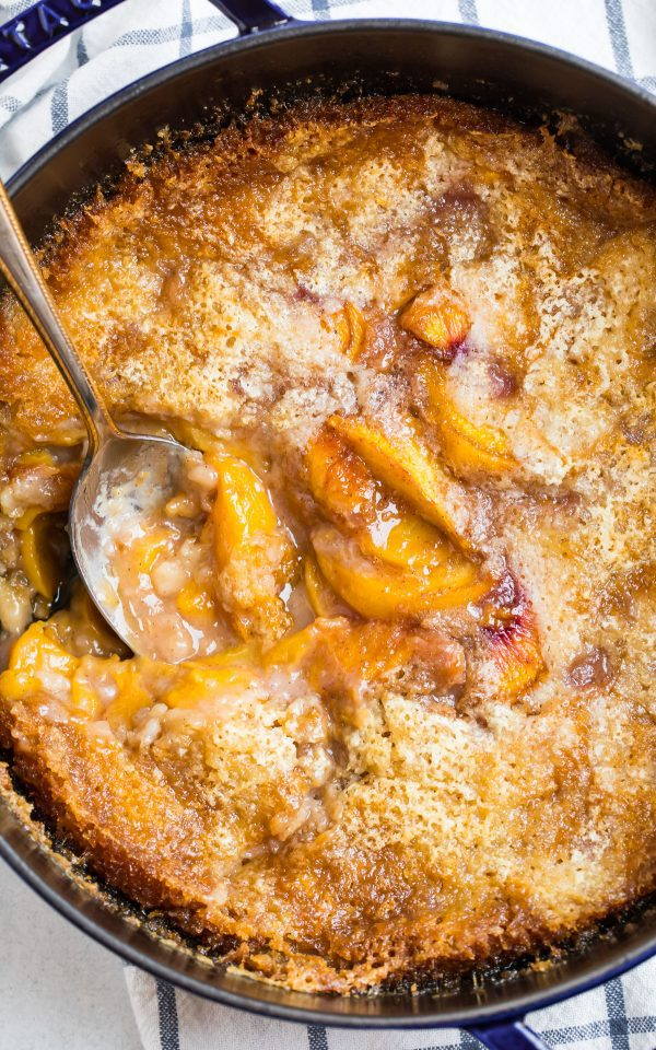 Dutch Oven Peach Cobbler made with fresh peaches cooked over campfire or in the oven