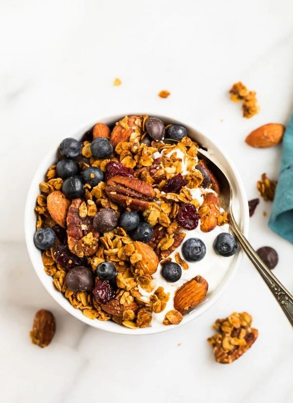 A bowl of the best healthy gluten free granola recipe with oats and honey served over yogurt