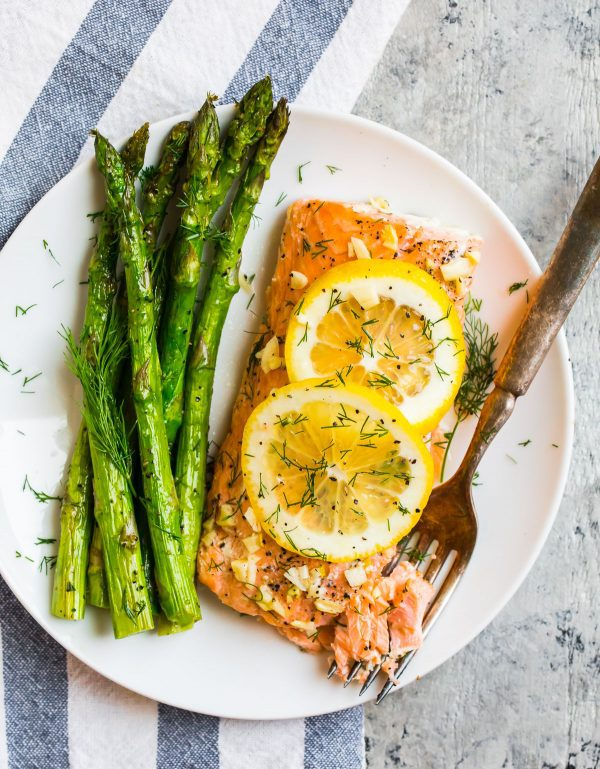 Grilled Salmon in Foil topped with lemon and dill and a side of grilled asparagus on a white plate