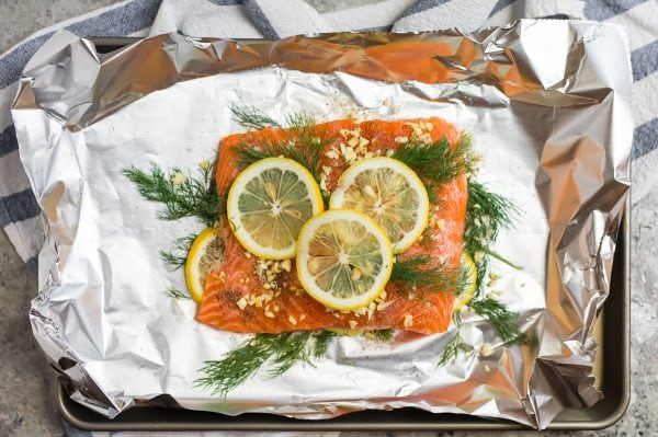 Fresh salmon, lemon slices, and dill on foil to be grilled for Grilled Salmon in Foil