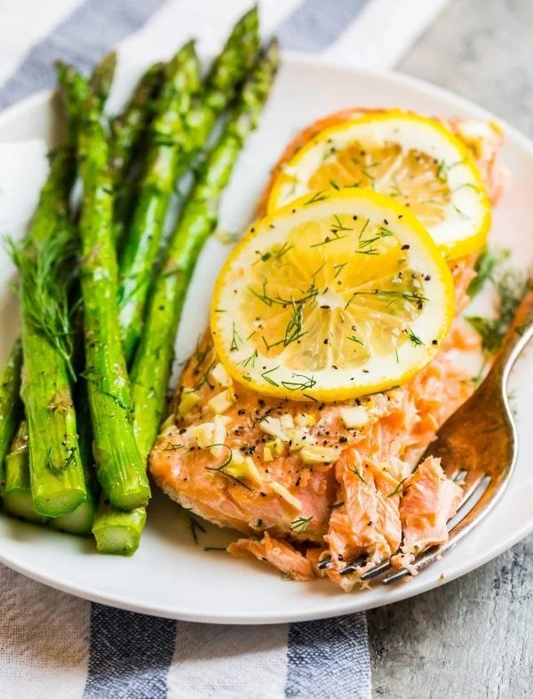 Asparagus, lemon, and dill served with Grilled Salmon in Foil on a white plate