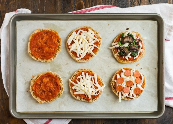 Healthy English Muffin Pizza with toppings for baking in the oven or to make ahead and freeze for later placed on a sheet pan with tomato sauce, pepperoni, vegetables, and fresh basil