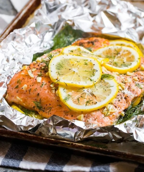 Best Grilled Salmon in Foil topped with dill and lemon to serve with vegetables