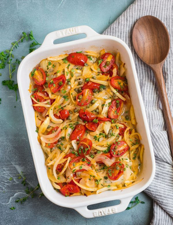 Healthy and simple Baked Cod in a baking dish served with tomatoes, capers, onions, and fennel