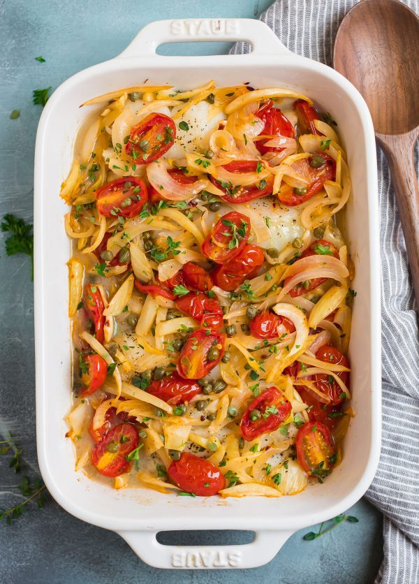 Healthy and simple Baked Cod in a baking dish with onions, tomatoes, fennel, and capers