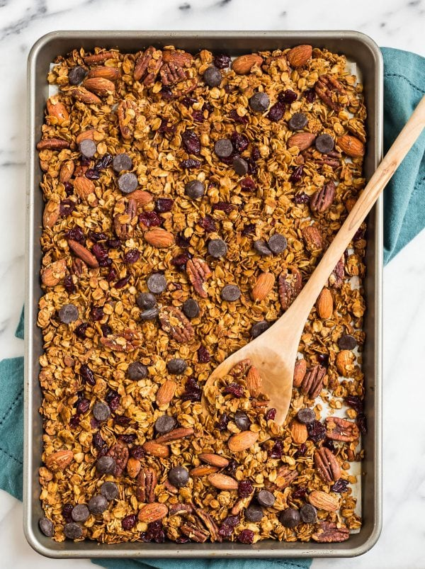 Healthy gluten free granola on a baking dish with the best ingredients like gluten free oats, nuts, and chocolate chips
