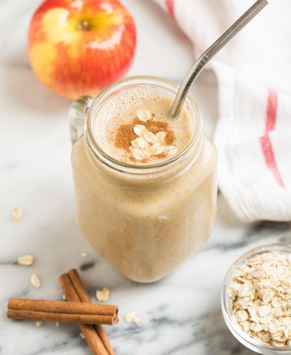 A mug with a creamy vegan apple smoothie with banana, oatmeal, and cinnamon