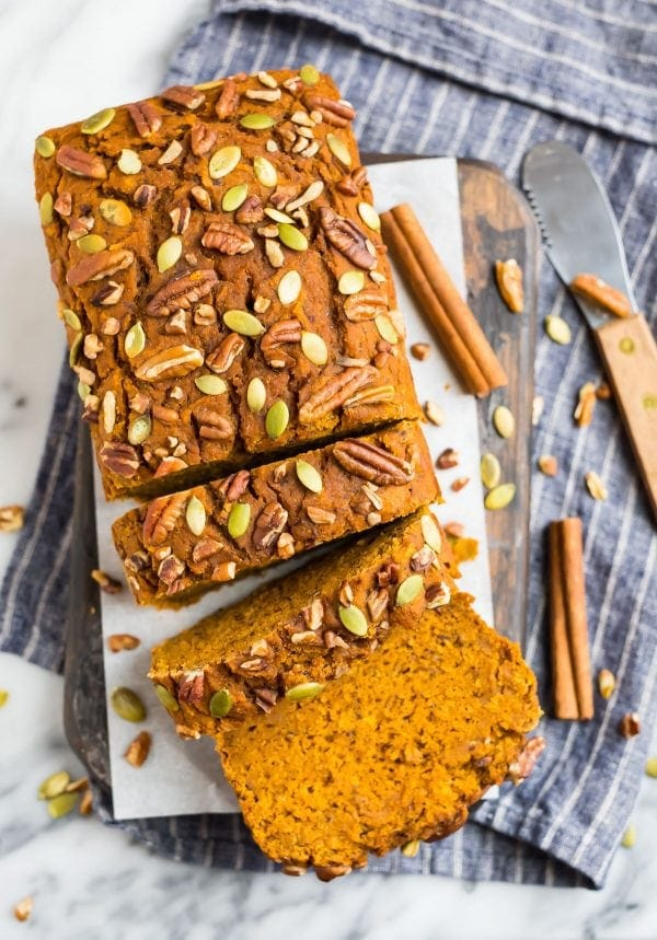 A loaf of moist vegan pumpkin bread made without oil and topped with pecans and pumpkin seeds for a healthy breakfast or snack