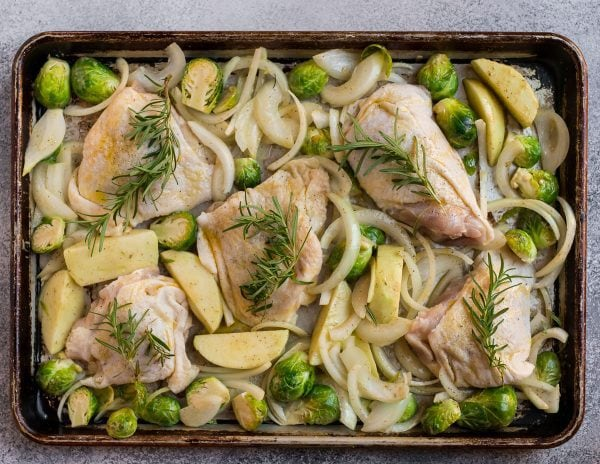 Crispy rosemary chicken thighs on a baking sheet with Brussels sprouts, apples, and onions