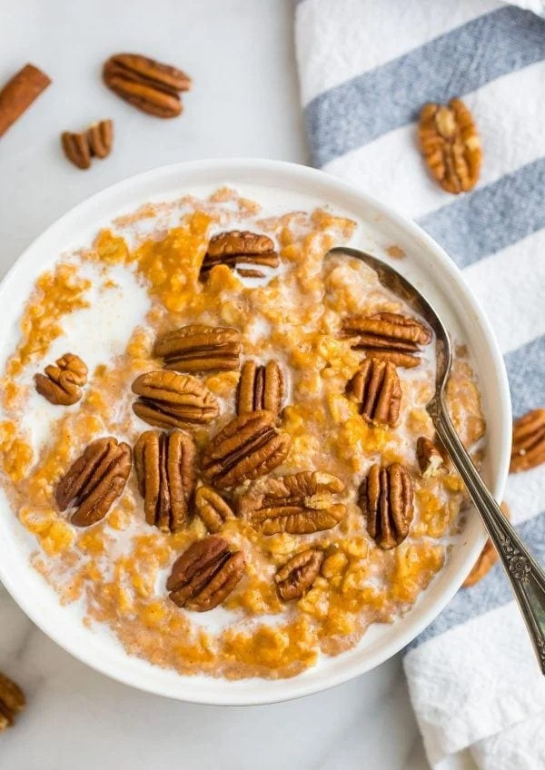 Healthy and delicious pumpkin oatmeal in a bowl topped with pecans