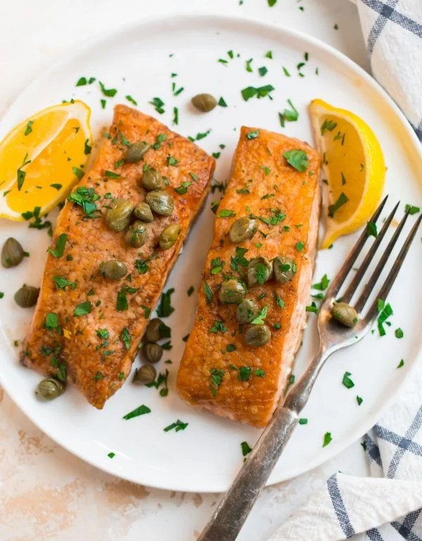 Healthy and easy salmon meuniere served on a plate with lemon and capers
