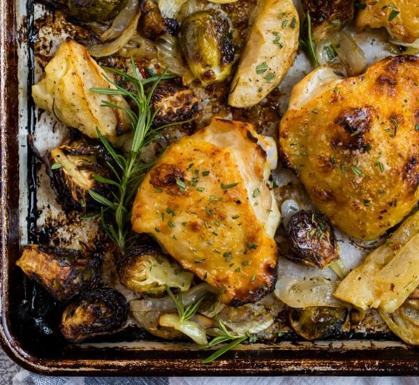 Crispy rosemary chicken thighs on a baking sheet with fresh rosemary, onions, apples, and Brussels sprouts
