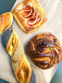 Danish pastries in Copenhagen, including a sesame braid, cinnamon bun, and apple croissant