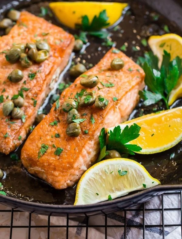 A skillet with two fillets of healthy salmon meuniere in a sauce of lemon and butter and topped with parsley