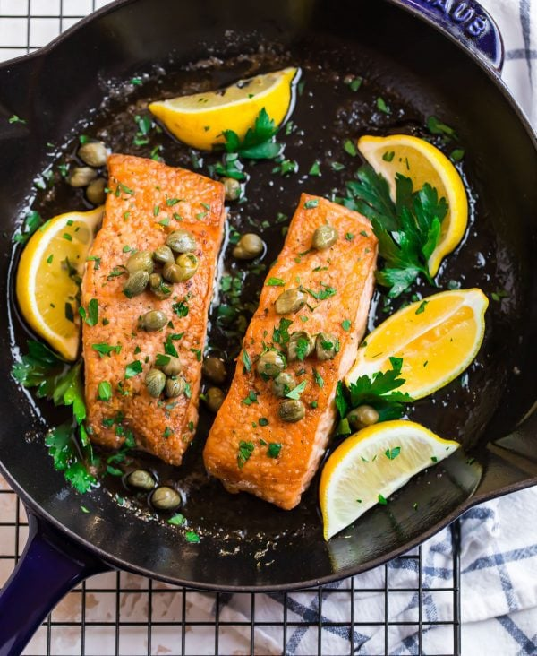 Two fillets of salmon meuniere in a skillet with fresh parsley and a lemon butter sauce