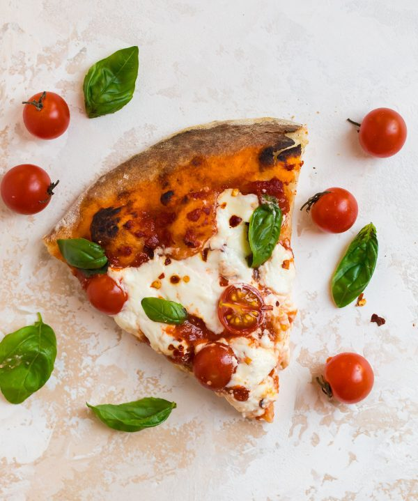 A Slice of Delicious Homemade Burrata Pizza Topped with Fresh Basil, Cherry Tomatoes, and Burrata Cheese