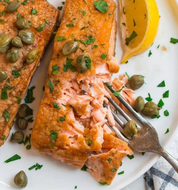 Salmon meuniere served on a plate with capers, lemon, and fresh parsley