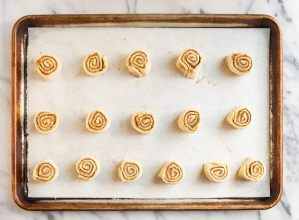 Puff pastry cinnamon rolls arranged on a baking sheet