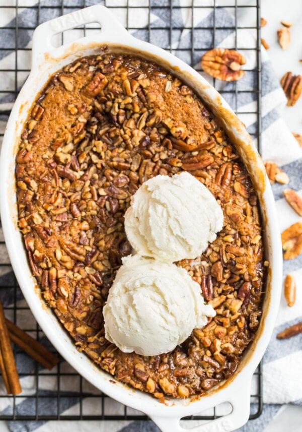 Amazing pecan pie cobbler served in a baking dish with vanilla ice cream