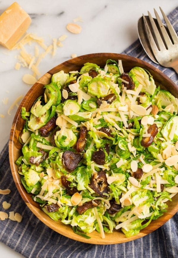 A wooden bowl with fresh shaved brussel sprouts slaw topped with dates, almonds, and Parmesan in a honey, lemon, and Dijon dressing