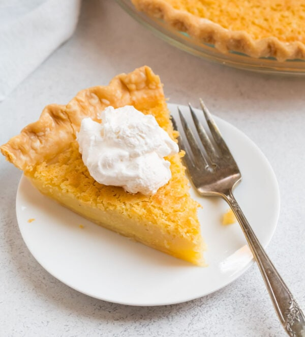A slice of the best buttermilk pie on plate topped with whipped cream