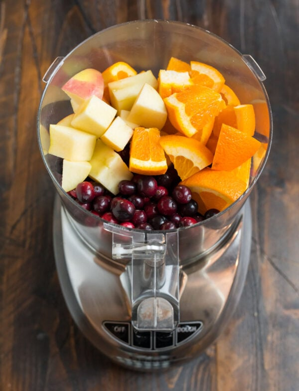 Apples, oranges, and cranberries in a food processor for making cranberry orange relish