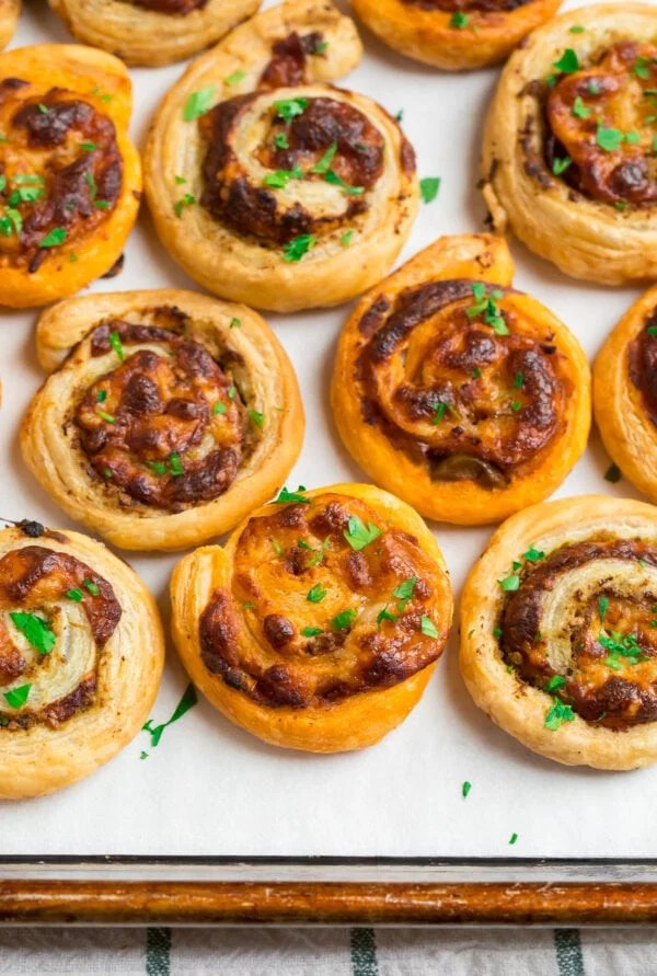 Pesto and cheese puff pastry pinwheels on a baking sheet