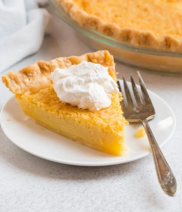 A slice of easy, old fashioned buttermilk pie served on a plate with whipped cream