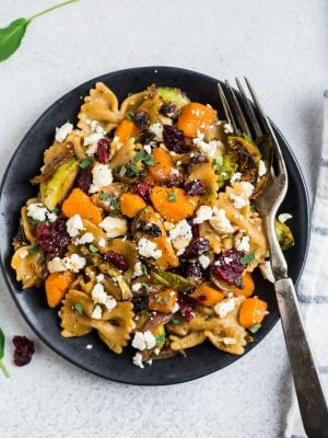 A plate with healthy sweet potato pasta with Brussel sprouts and cranberries on a black plate.